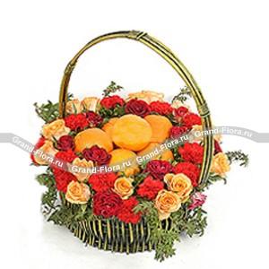 Корзина с фруктами и цветами РадостьХотите кого-то удивить и обрадовать? Тогда оформите доставку корзины с фруктами и цветами Радость. Яркая, красочная и оригинальная, она поднимет настроение любому.<br>Большая круглая плетеная корзина украшена розами , гвоздиками и яркой зеленью, а вну...<br>